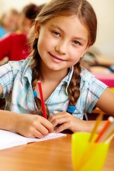 Estudiante sonriente sujetando un lápiz rojo