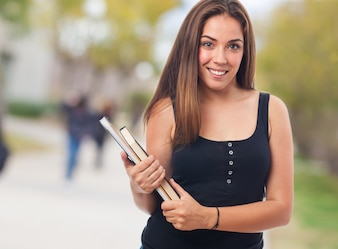 Estudiante sonriente sujetando unos libros