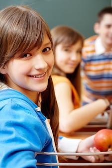Estudiante sosteniendo una manzana en clase