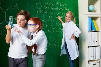 Estudiantes analizando el experimento con profesora de fondo