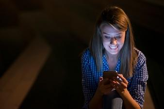 Excited hermosa chica recibiendo un mensaje sms con buenas noticias en un teléfono móvil fuera