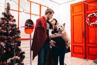 Excited pareja ingenio perro en casa decorada
