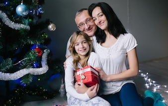 Familia con caja de regalo en el árbol de Navidad