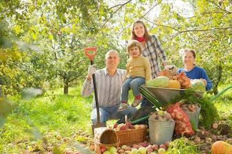 Familia feliz con la cosecha en el jardín