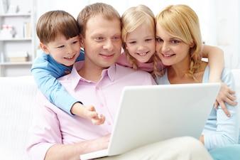 Familia prestando atención al ordenador portátil
