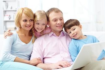 Familia relajada con el ordenador portátil