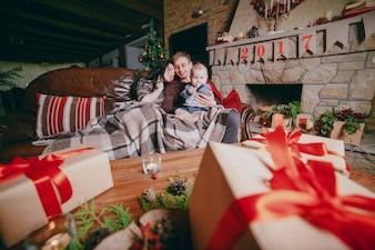 Familia sentada en el sofá arropada con una manta y visto desde los regalos marrones de la mesa