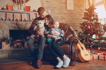 Familia sentada en un sofá con el perro en navidad