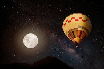 Fantasía hermosa del globo del aire caliente y de la Luna Llena con la estrella de la manera lechosa en fondo de los cielos de la noche. Ilustraciones de estilo retro con tono de color vintage