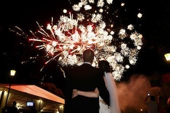 Feliz abrazos novia y el novio viendo hermoso colorido fuegos artificiales cielo nocturno