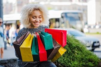Feliz cliente femenino con bolsas de papel