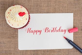 Feliz cumpleaños cupcake con pluma roja