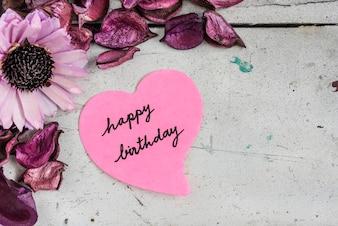 Feliz cumpleaños nota en forma de corazón de papel con flores de color rosa