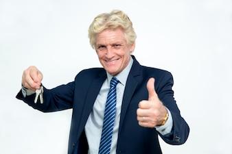 Feliz de negocios mayor Muestra Claves y el pulgar
