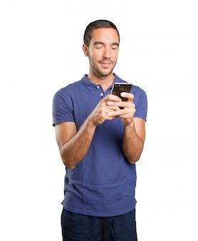 Feliz joven utilizando un teléfono móvil sobre fondo blanco