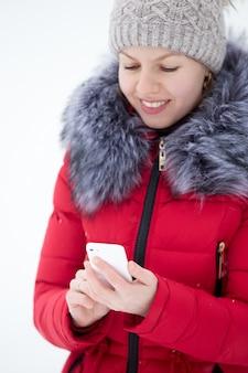 Feliz mujer sonriente en chaqueta de invierno rojo SMS con teléfono móvil, al aire libre contra la nieve