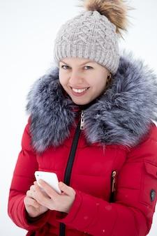 Feliz mujer sonriente en chaqueta de invierno rojo texting con teléfono móvil, al aire libre contra la nieve, mira en cámara
