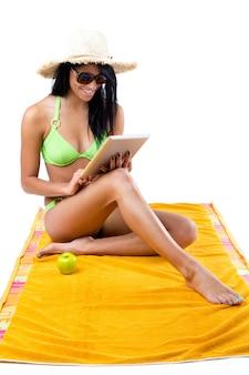Feliz niña con bikini verde y mesa digital