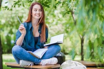 Feliz niña estudiando en el parque