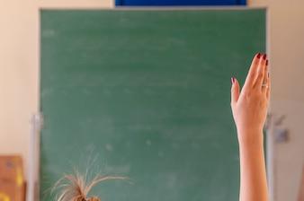Feliz niña levantó las manos en el aula