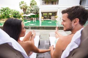 Feliz, pareja, tenencia, manos, descansar, cerca, piscina