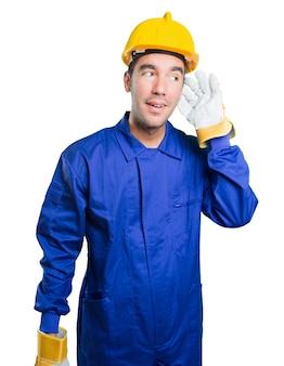 Feliz trabajador con escuchar gesto sobre fondo blanco