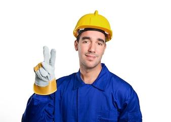 Feliz trabajador con gesto de la victoria sobre fondo blanco