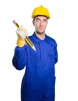 Feliz trabajador utilizando un gran lápiz sobre fondo blanco