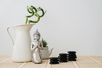 Figura de buda en frente de planta de bambú y piedras volcánicas