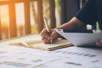 Firma de las mujeres de negocios en el documento