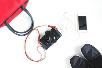 Flat lay de artículos de viaje con cámara de película, smartphone, bolso de mano rojo y zapatillas de deporte