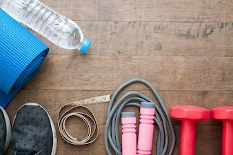 Flat lay de equipos deportivos y botella de agua y cinta métrica sobre fondo de madera con espacio de copia