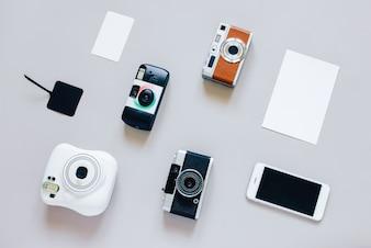 Flat lay de varias cámaras estilo con smartphone y tarjeta en blanco, diseño mínimo