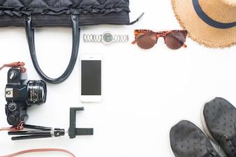 Flat lay of woman accesorios con cámara de película de teléfono móvil y elementos de color negro sobre fondo blanco, concepto de estilo de vida, vista desde arriba