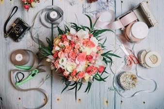 Flatlay de ramo de boda naranja y cintas en la mesa de trabajo