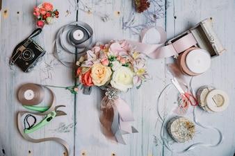 Flatlay del ramo de la boda, cintas y cámara