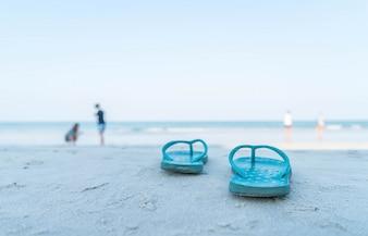 Flipflops en una playa de arena del océano