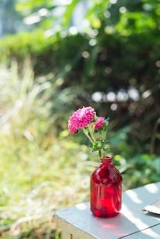 Flor decorativa en una botella roja