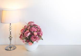 Florero blanco con flores rosas