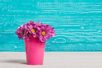 Florero con flores moradas y fondo de madera