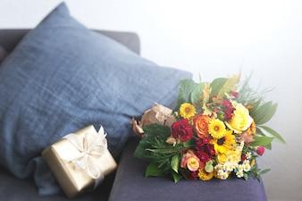Flores en un sofá con un regalo