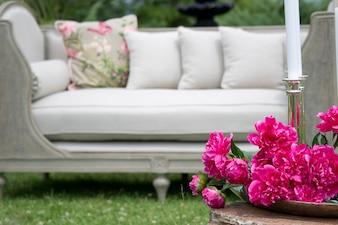 Flores rosas con un sofá blanco de fondo