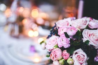 Flores rosas en un jarrón con una mesa desenfocada de fondo