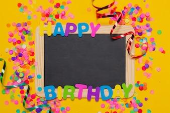 Fondo amarillo con las letras  happy birthday  y una pizarra