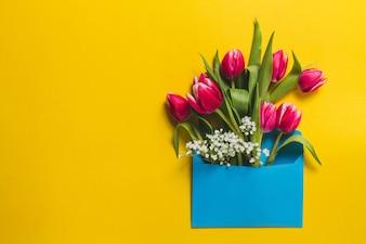 Fondo amarillo con sobre azul y tulipanes