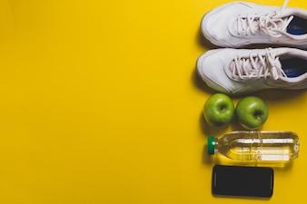 Fondo amarillo con teléfono móvil, zapatillas y manzanas