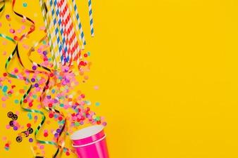 Fondo amarillo con vasos y decoración de fiesta