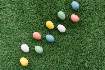 Fondo de hierba con huevos de pascua en diferentes colores