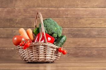 Fondo de madera con cesta llena de verduras