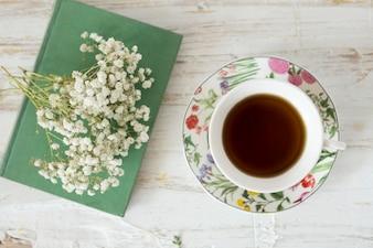 Fondo de madera con taza de café, flores y libro